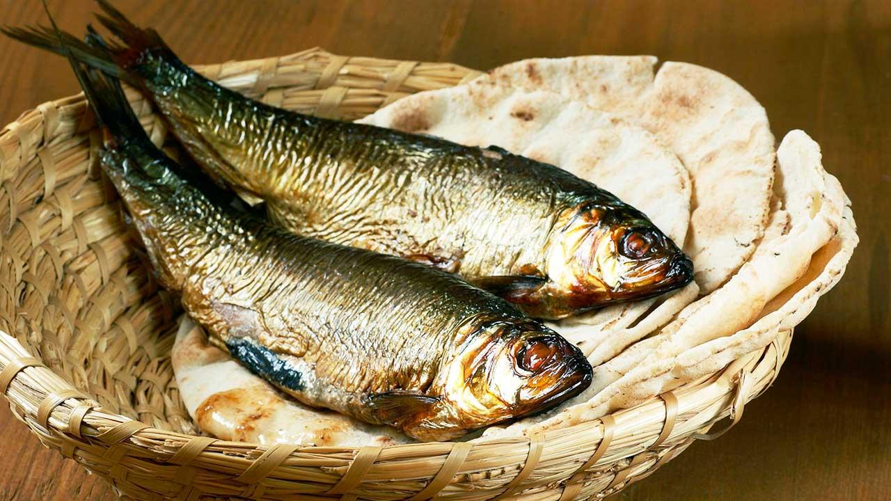Flechtkorb mit Fischen und Fladenbroten