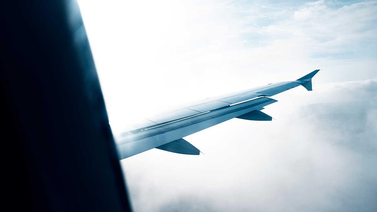 Flügel eines Flugzeugs über den Wolken