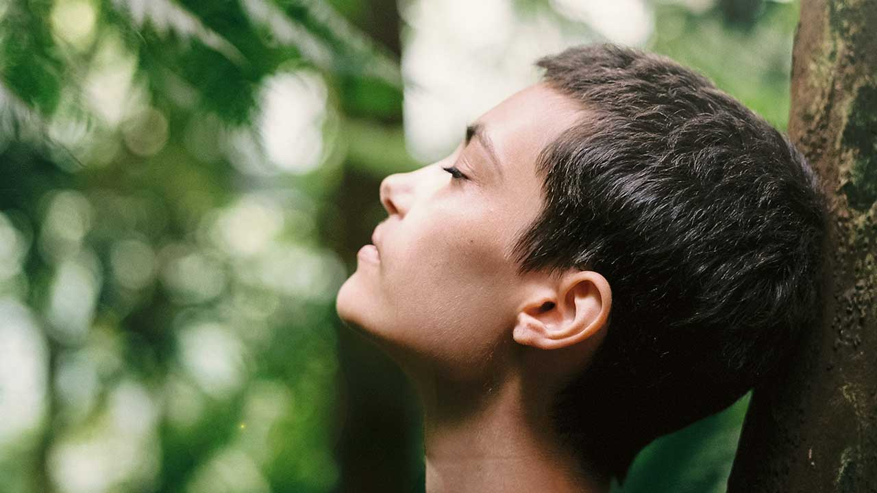 Frau mit geschlossenen Augen lehnt sich an einem Baumstamm an