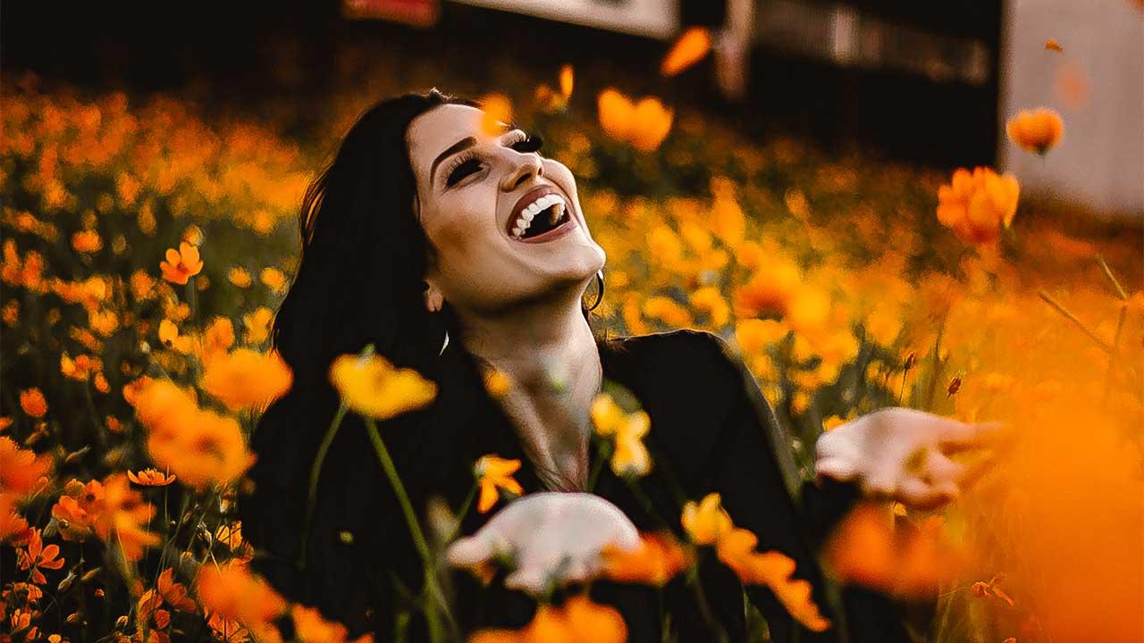 Lachende Frau in einem orangen Blumenfeld