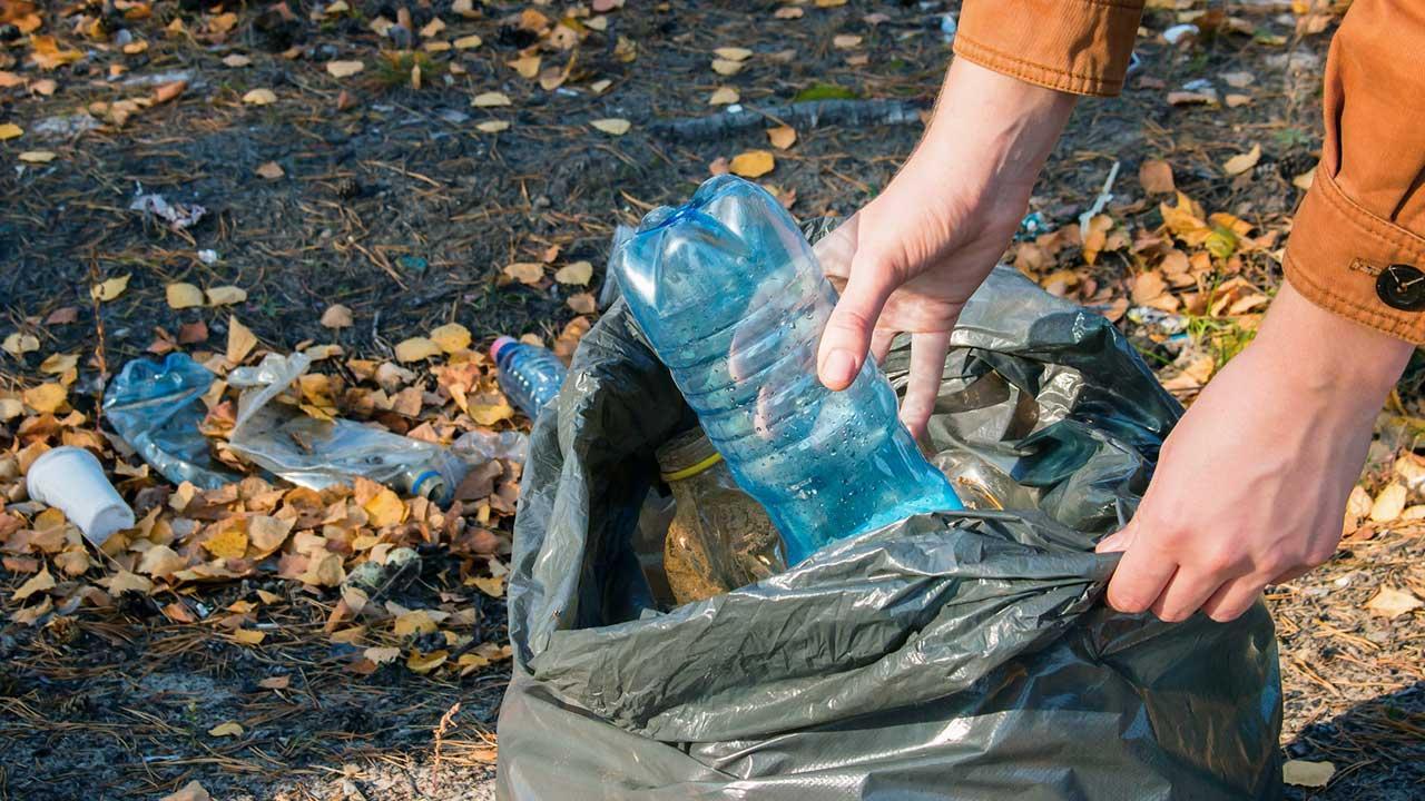 Hände werfen eine Plastikflasche in einen Abfallsack