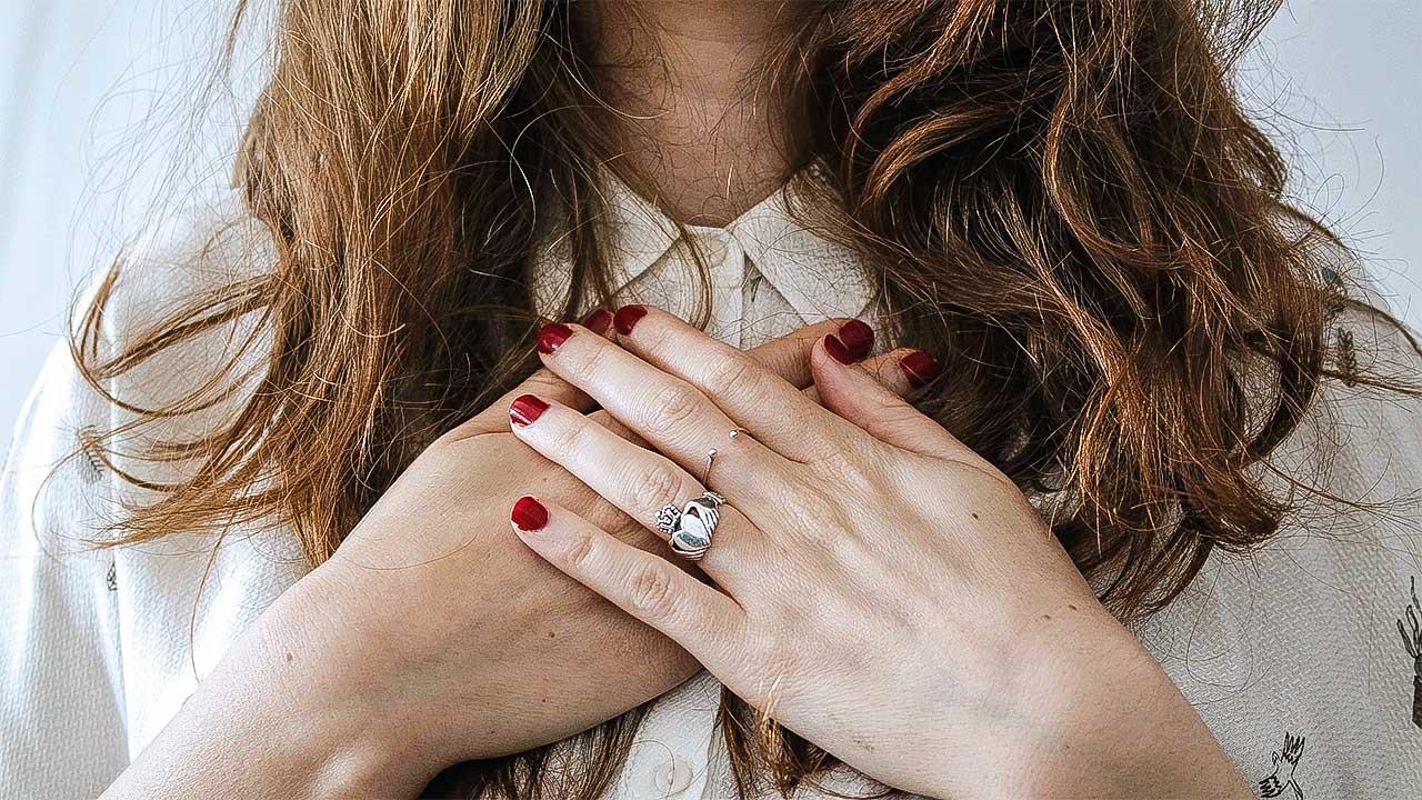 gekreuzte Hände vor einer Frauenbrust