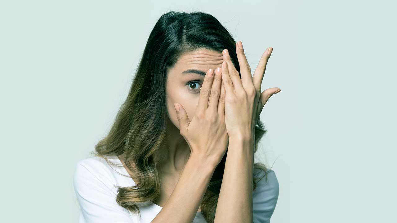 Frau verdeckt mit ihren Händen ein Auge
