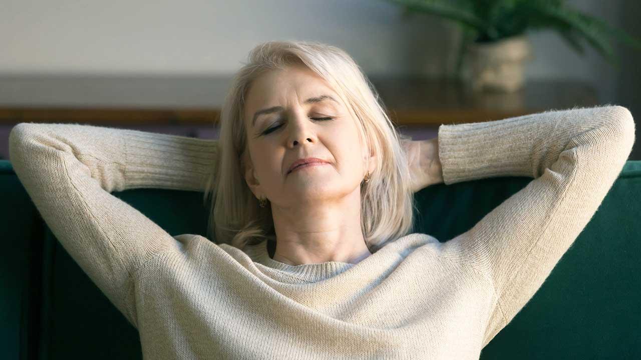Frau verschränkt Hände hinter dem Kopf und hält die Augen geschlossen