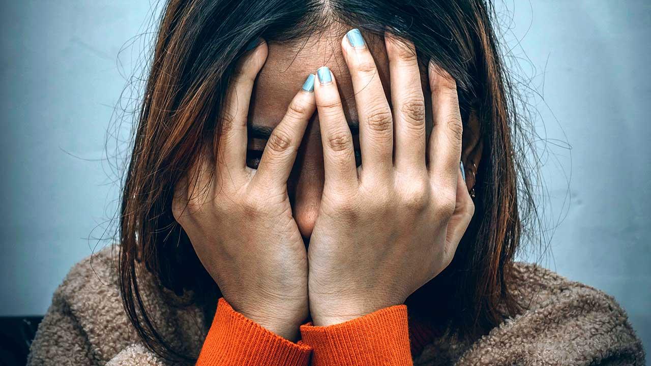 Junge Frau hält Hände vor das Gesicht
