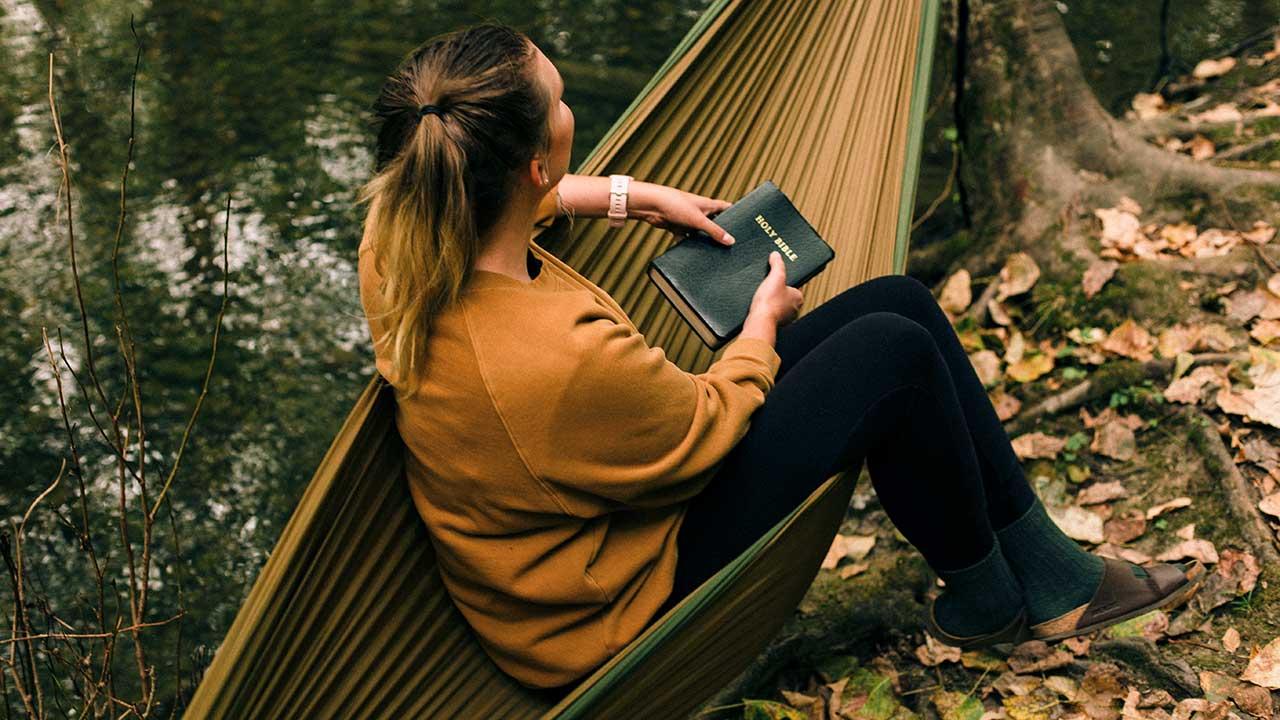 Frau mit einer Bibel in den Händen sitzt auf einer Hängematte