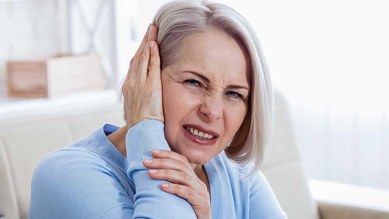 Frau hält Hand an Ohr, weil sie Ohrenschmerzen hat