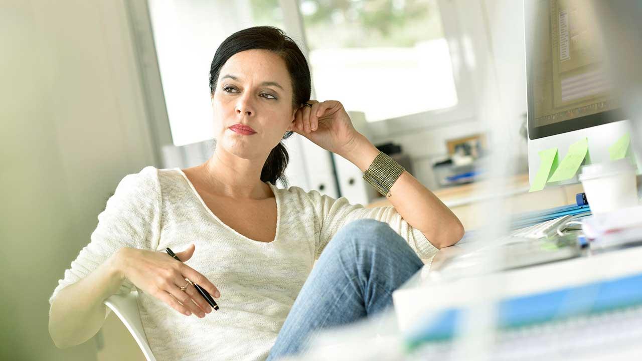 Frau sitzt vor Schreibtisch und überlegt intensiv
