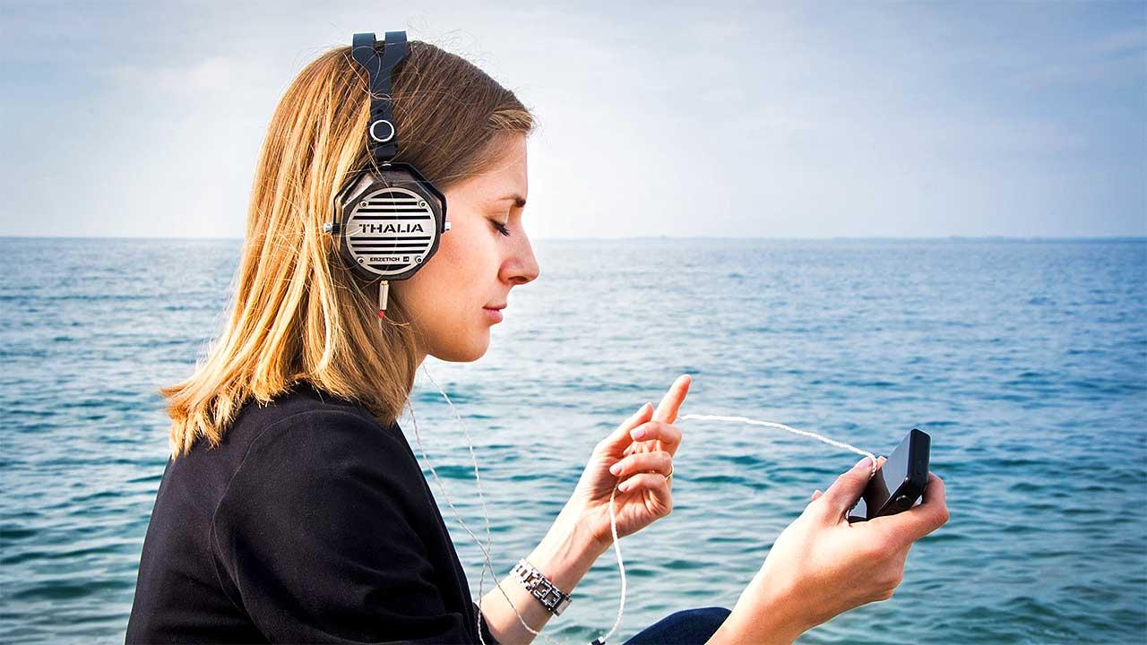 Junge Frau sitzt am Meer und hört mit Kopfhörern Musik