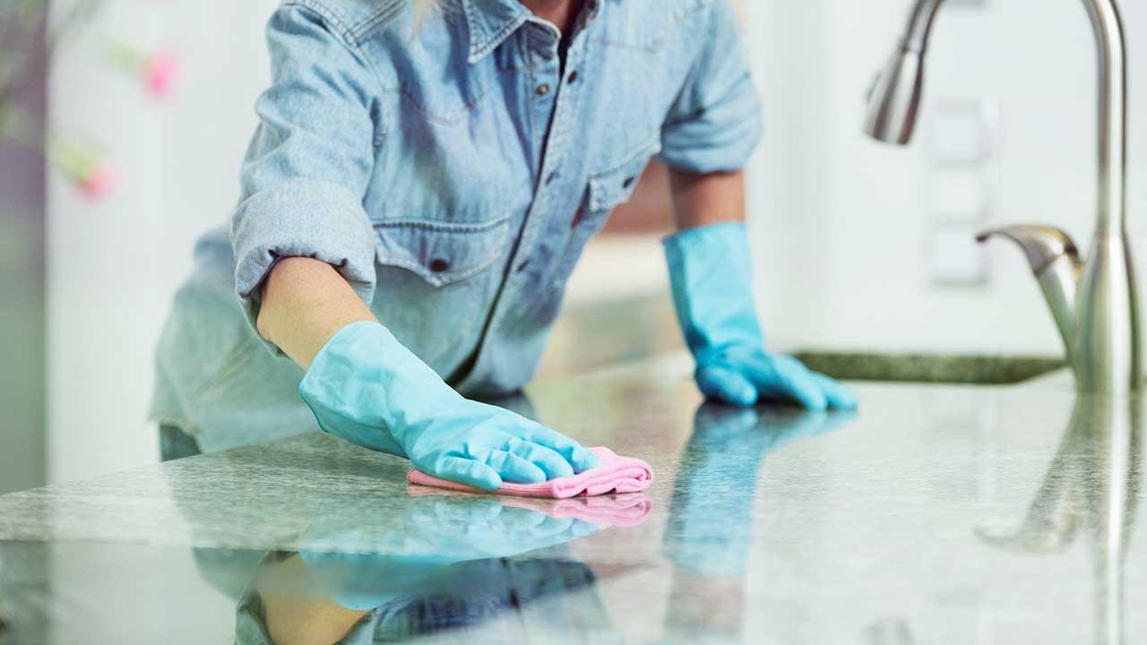 Frau reinigt mit einem Lappen die Oberfläche der Küche