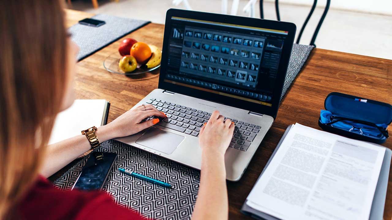 Frau macht Homeoffice und sitzt mit ihrem Laptop und ihren Unterlagen am Tisch