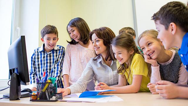 Lehrerin und Schüler vor Computer