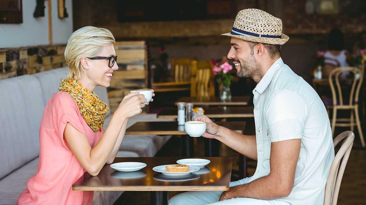Frau und Mann sitzen lächelnd in einem Café