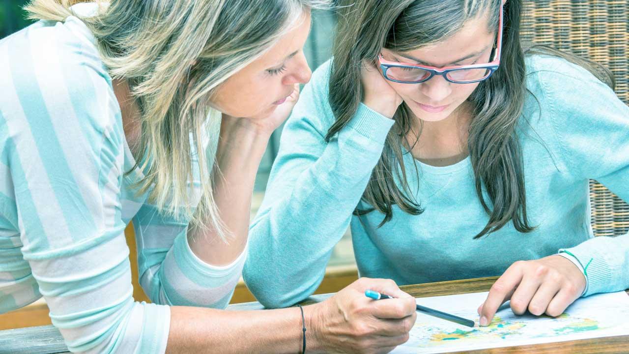 Mutter hilft ihrer Tochter bei den Hausaufgaben