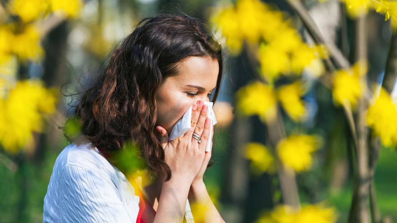 Frau niest in ein Taschentuch mit gelben Blumen im Hintergrund