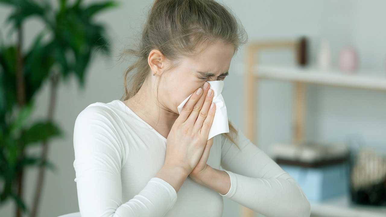 Junge Frau niest in ein Taschentuch