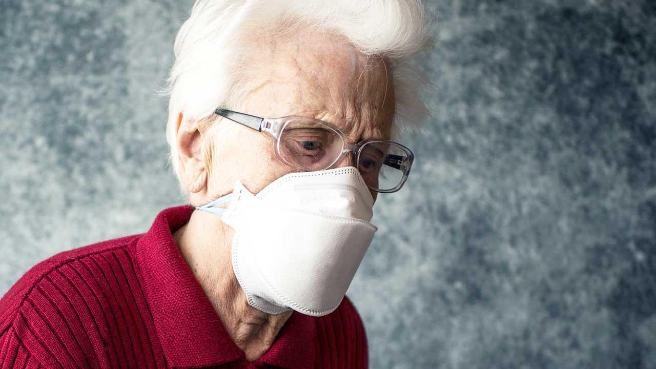 Senorin trägt Gesichtsmaske als Schutz vor Coronavirus
