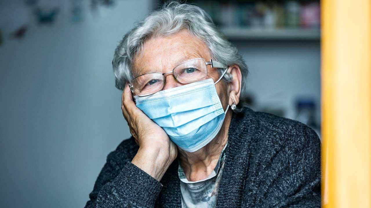 Nachdenkliche Seniorin mit Gesichtsmaske