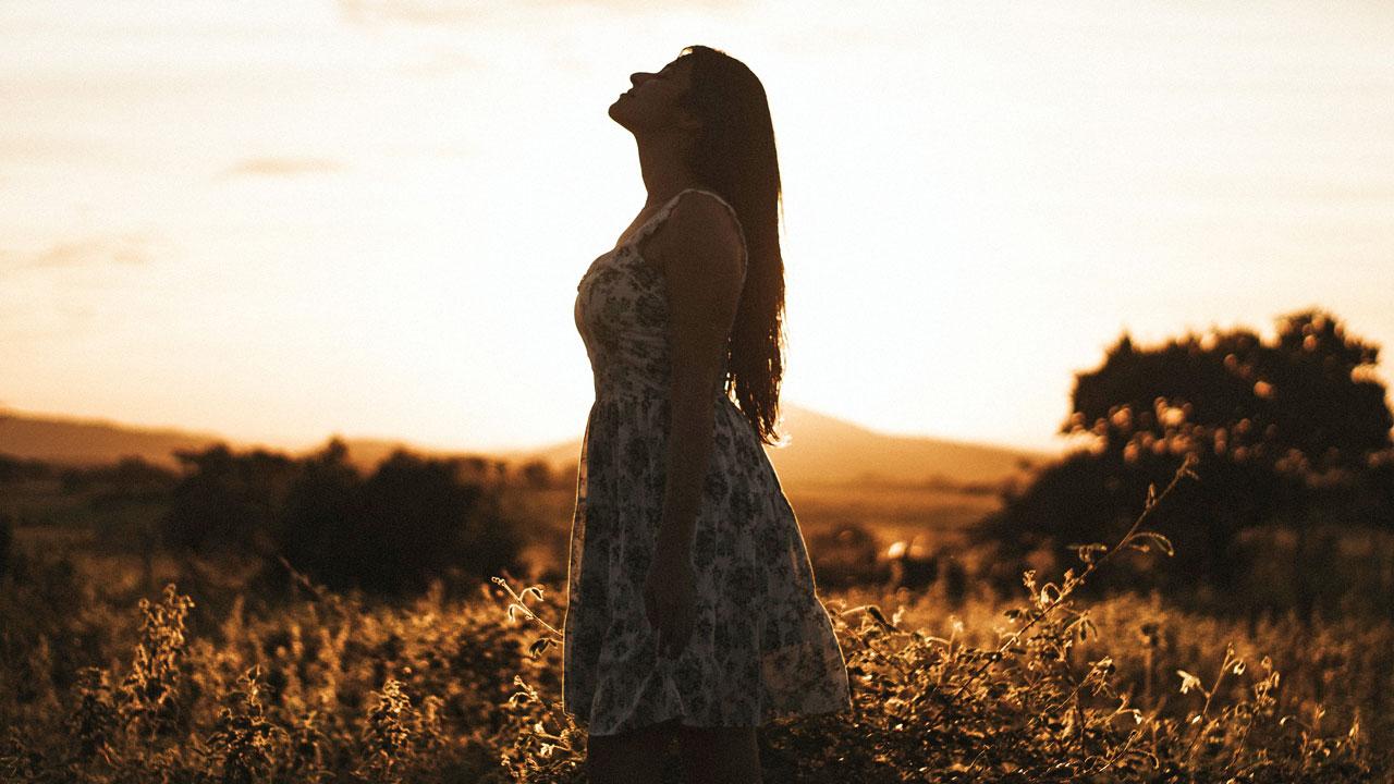 Eine Frau als Silhouette abgebildet blickt nach oben