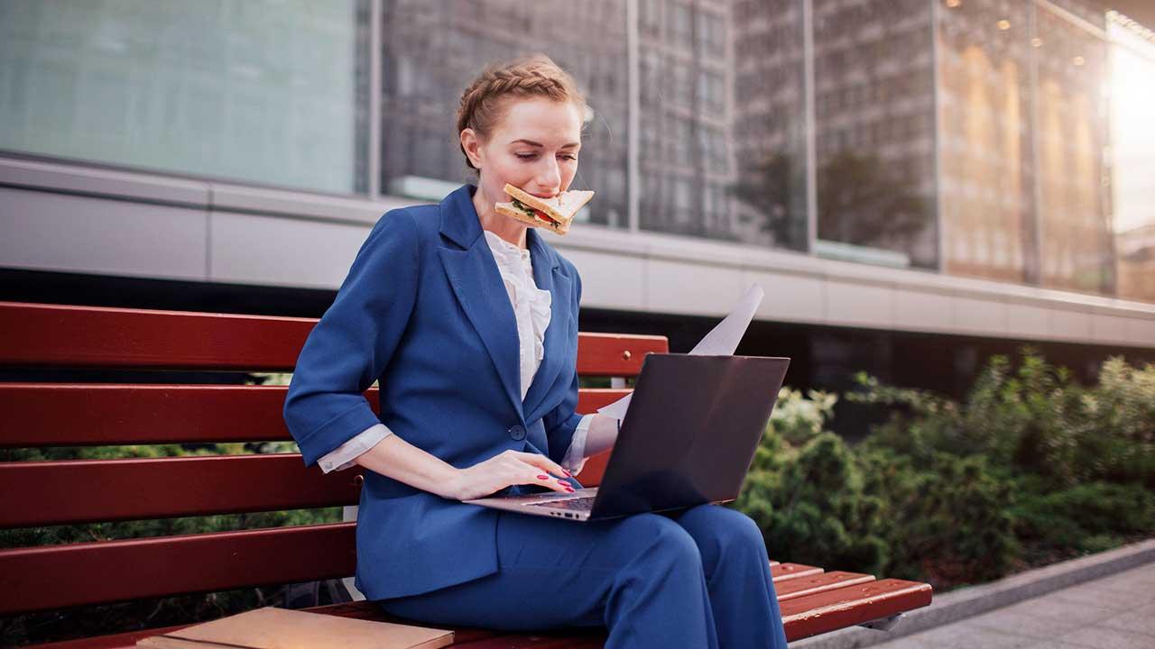 Geschäftsfrau auf Sitzbank arbeitet und isst gleichzeitig