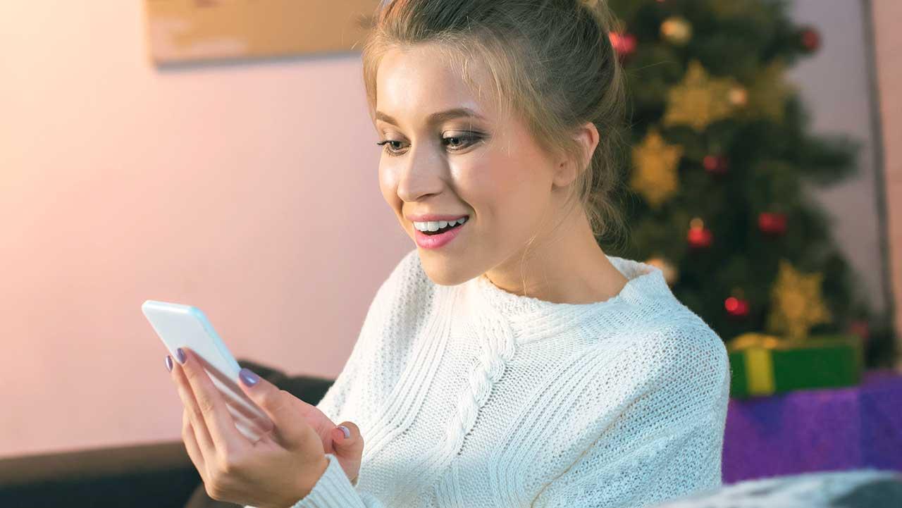 Frau sitzt auf Sofa mit Weihnachtsbaum im Hintergrund und hält Smartphone in der Hand