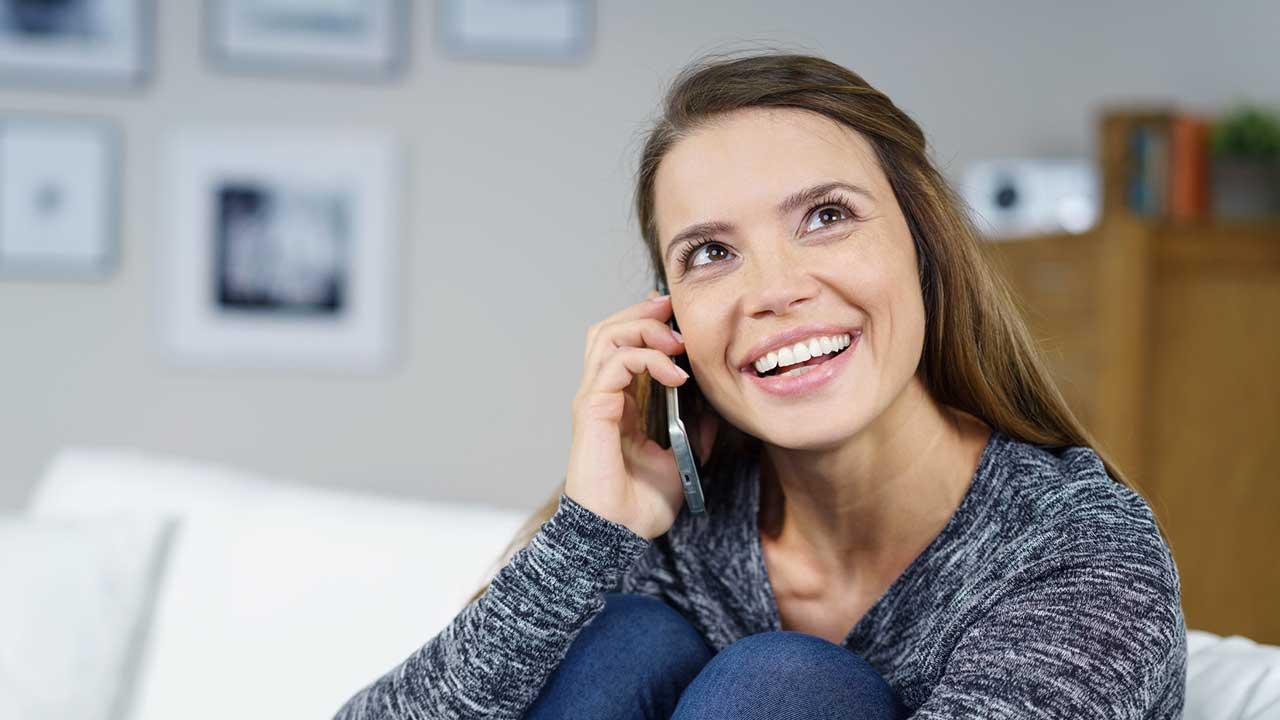 Frau telefoniert und freut sich