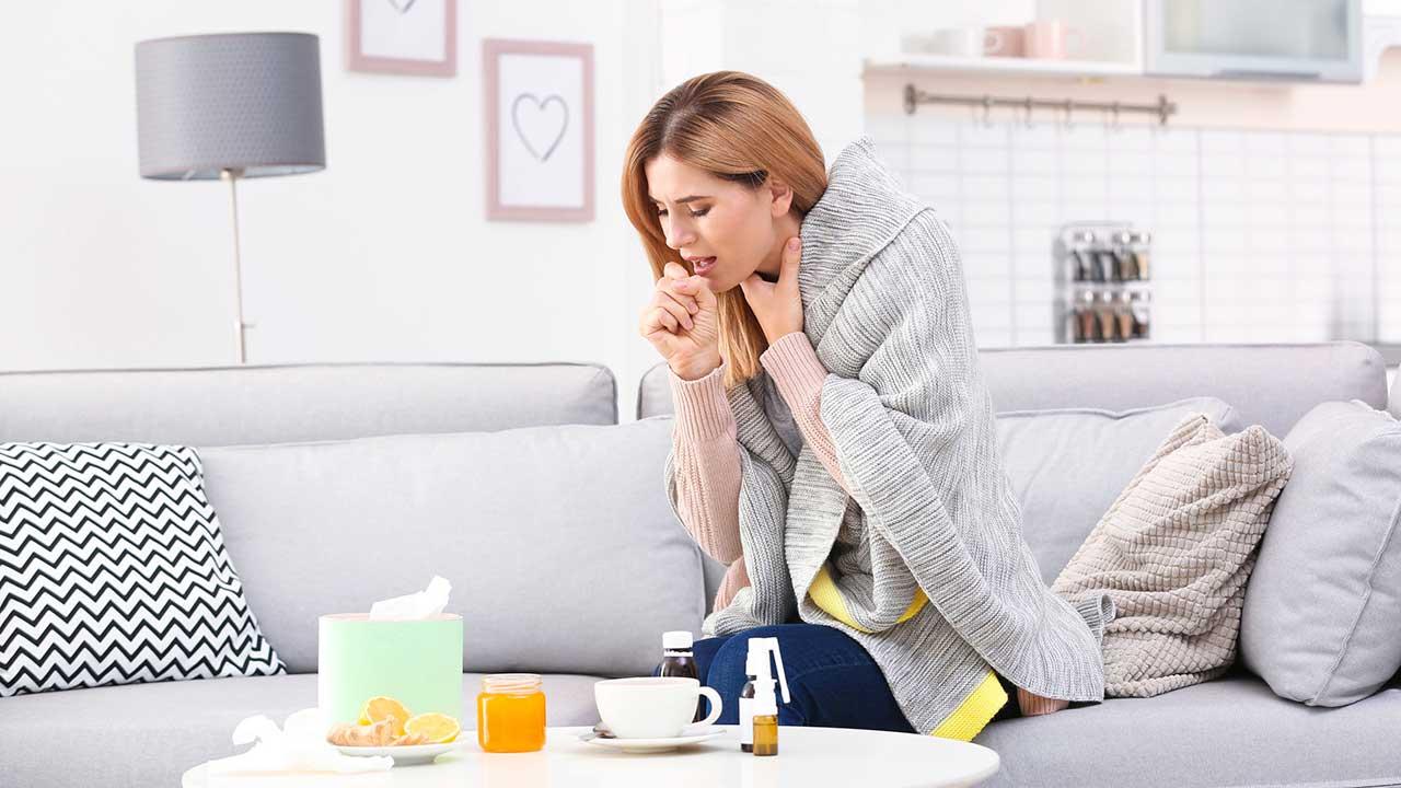 Frau sitzt auf einem Sofa und hustet