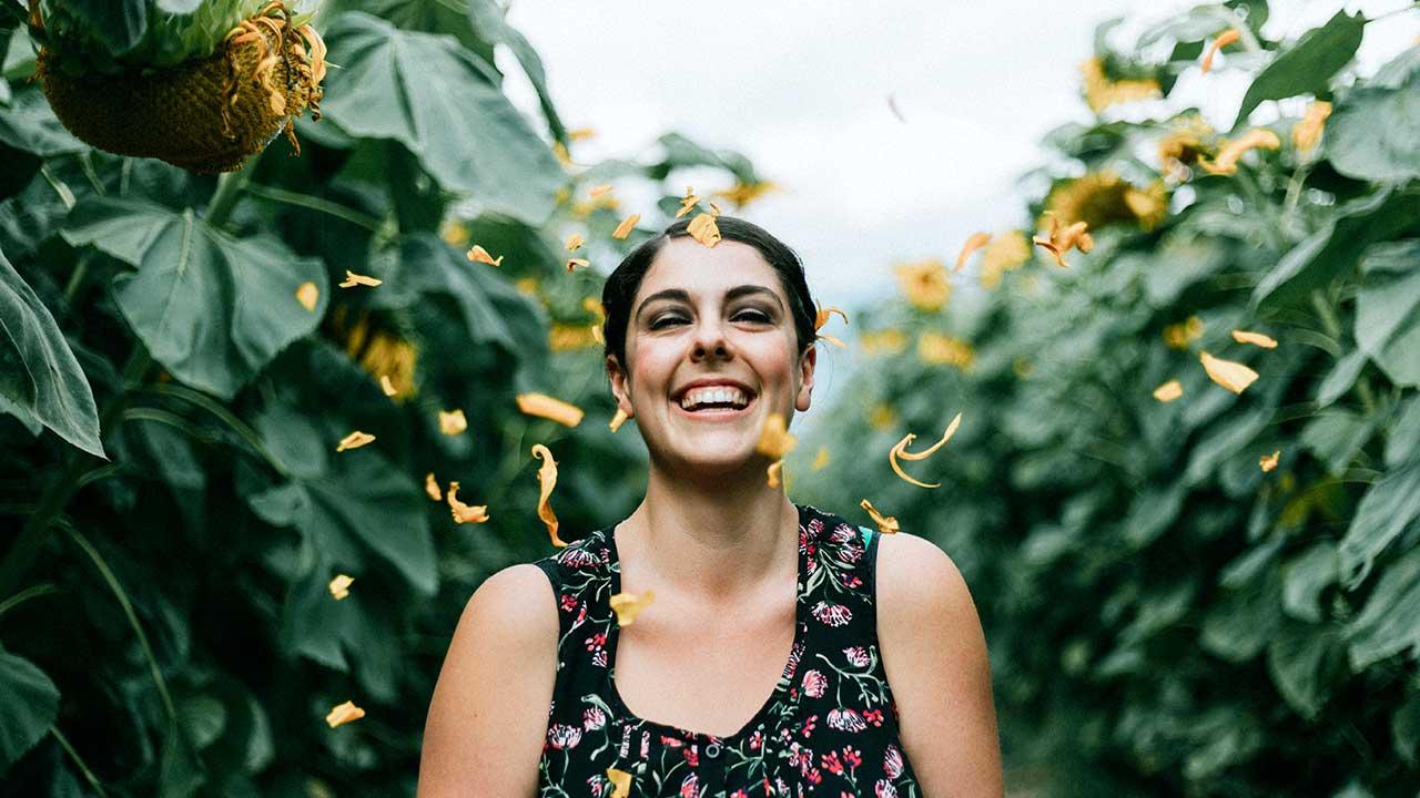 Eine Frau steht in einem Sonnenblumenfeld und freut sich an vorbeifliegenden Blättern einer Sonnenblume