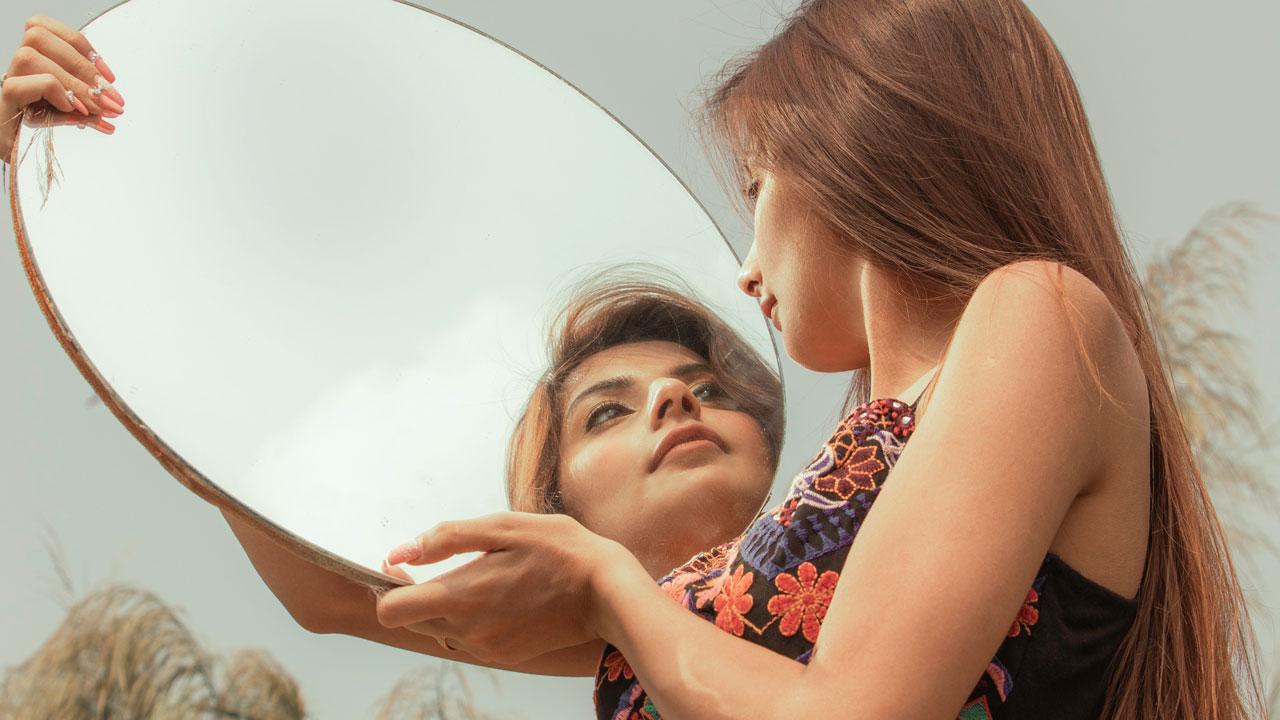 Eine Frau schaut sich im Spiegel an