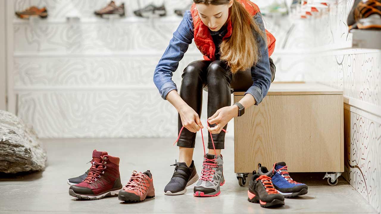 Frau probiert in einem Sportgeschäft Wanderschuhe an