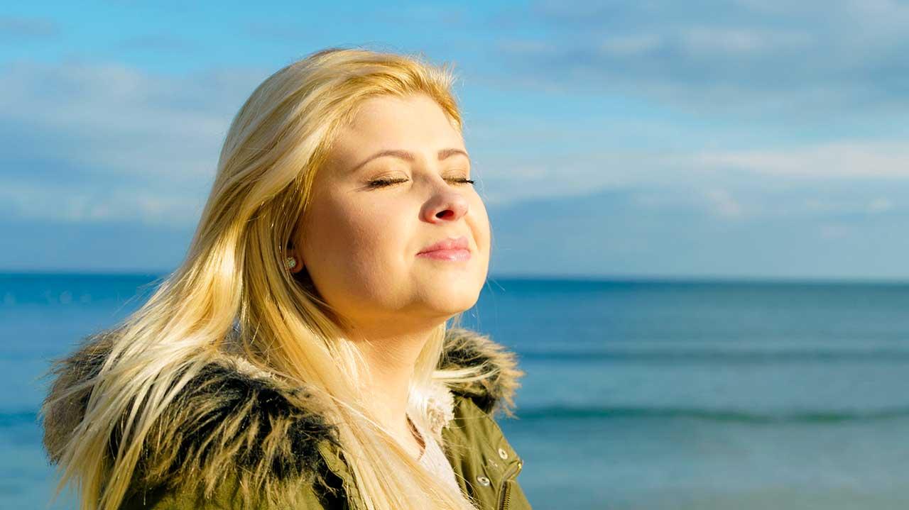 Frau mit geschlossenen Augen geniesst Sonnenlicht und Wärme