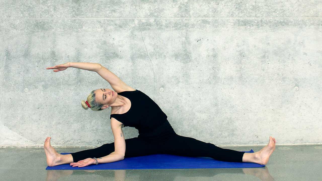 Stretching-Übung in der Grätsche am Boden