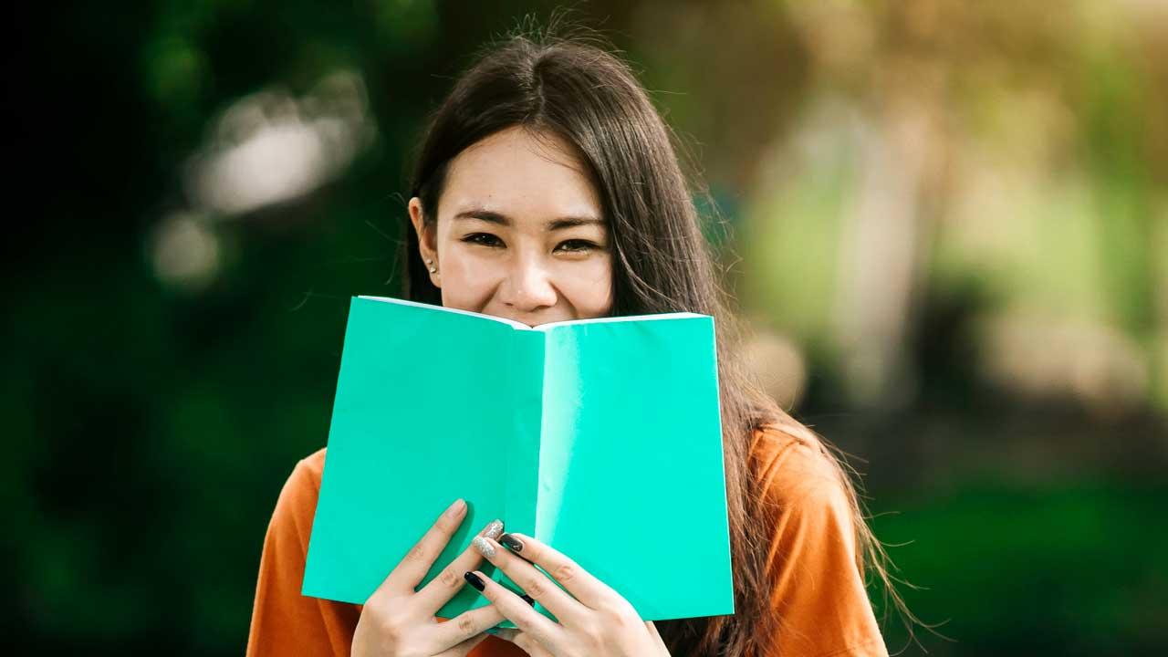 Junge Frau hält Buch vor ihren lachenden Mund