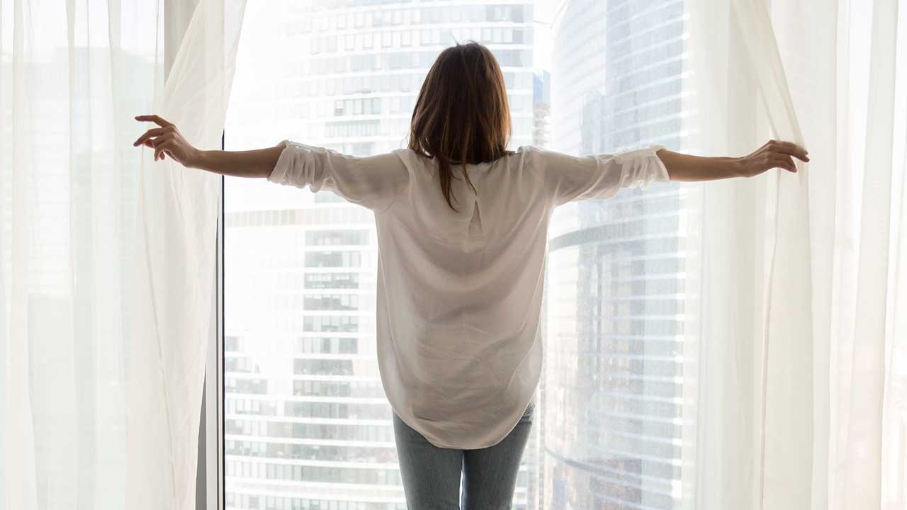 Frau am offenen Fenster