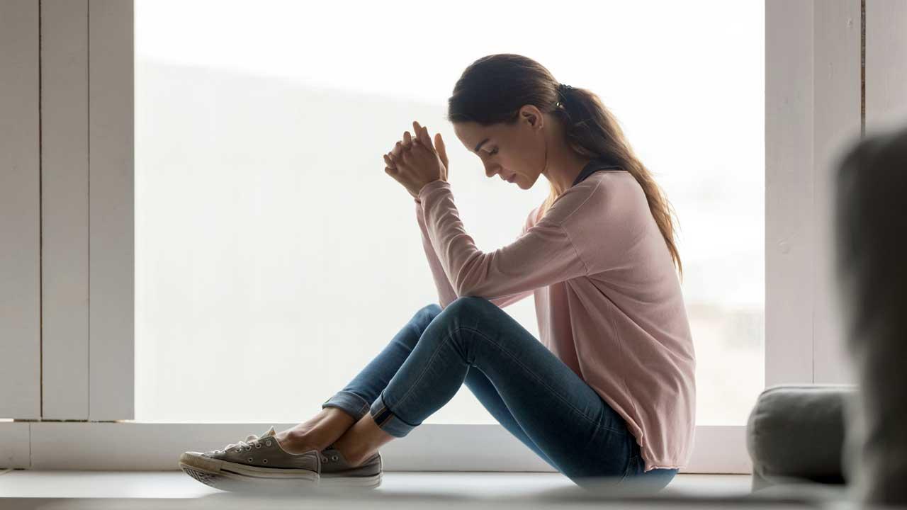 Sehr nachdenkliche Frau sitzt in ihrer Wohnung vor einem grossen Fenster