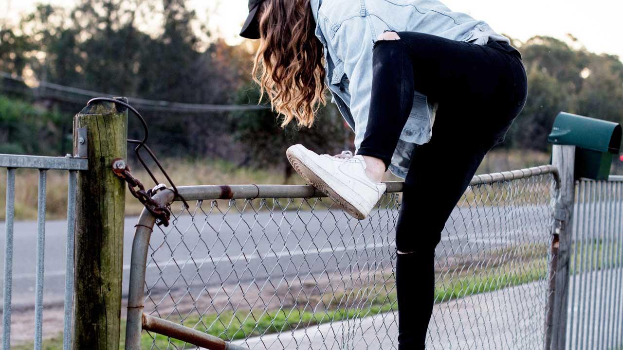 Junge Frau klettert über einen Zaun