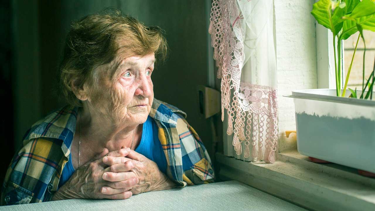 Ältere, einsame Frau sitzt an einem Tisch bei einem Fenster und sieht bedrückt aus