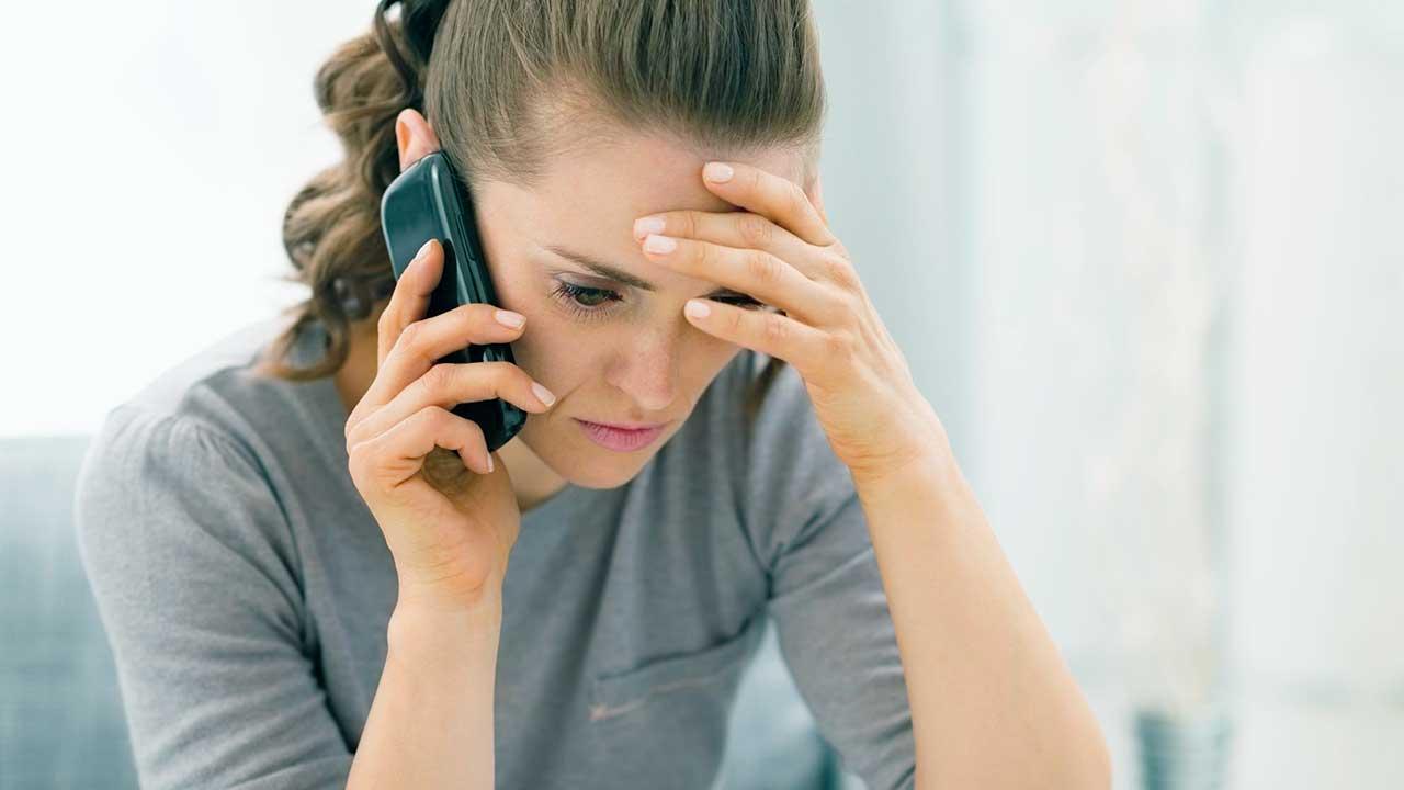 Frau niedergeschlagen am Telefon