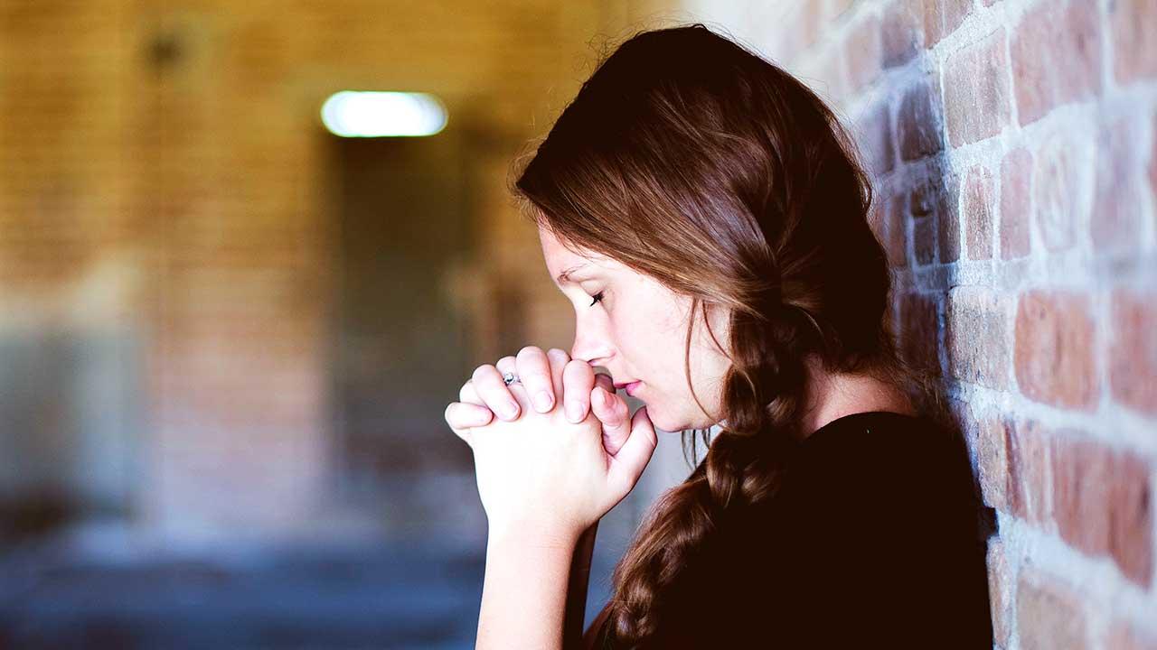 Frau ist angelehnt an eine Backsteinmauer und betet mit Hingabe