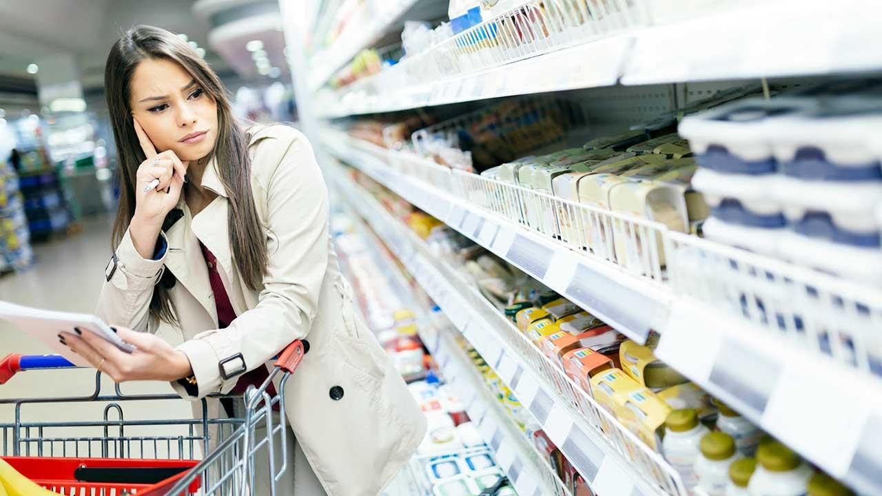 Frau steht im Supermarkt vor dem Regal und denkt nach