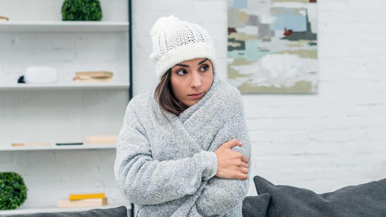 Frau ist warm angezogen und friert trotzdem in ihrer Wohnung