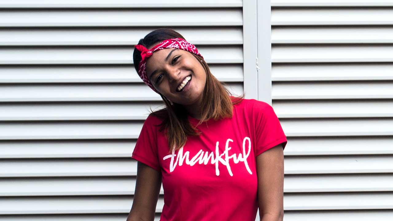 Fröhlich Frau trägt rotes T-Shirt mit der Aufschrift «thankful»