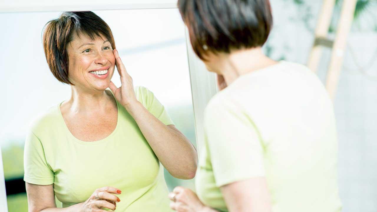 Frau steht vor Spiegel und ist zufrieden mit dem Äusseren