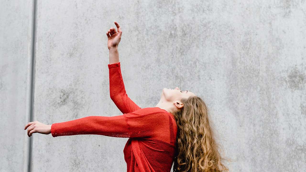 Junge Frau in rot ist ins Tanzen vertieft
