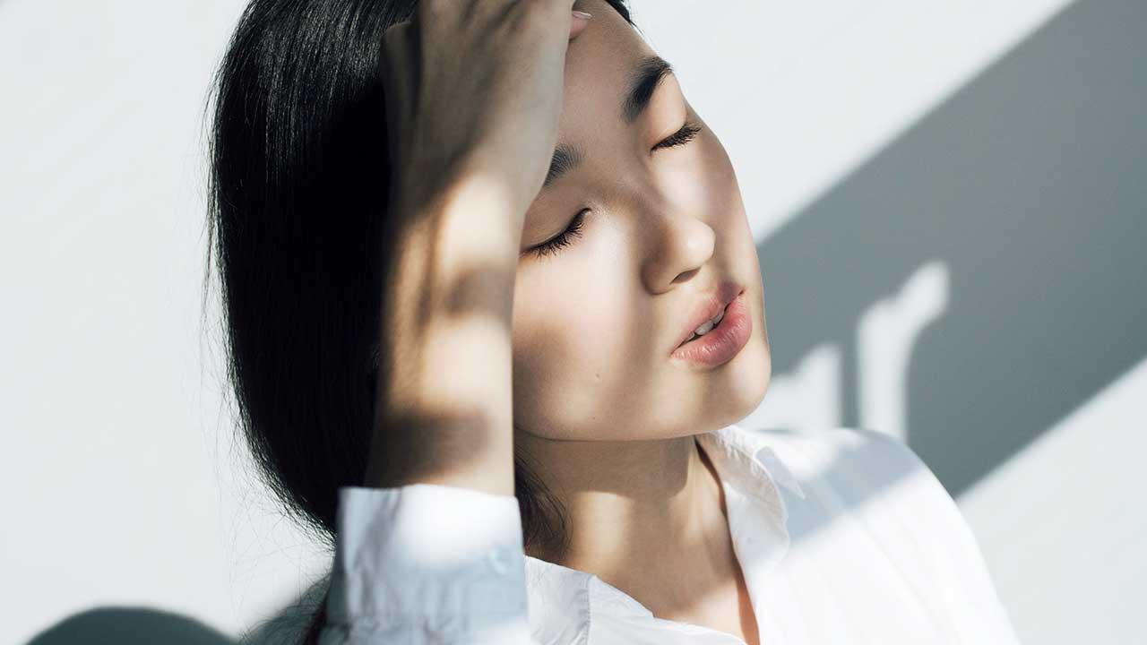Schatten fällt auf das Gesicht einer jungen Frau, welche die Augen geschlossen hält und sich ausruht