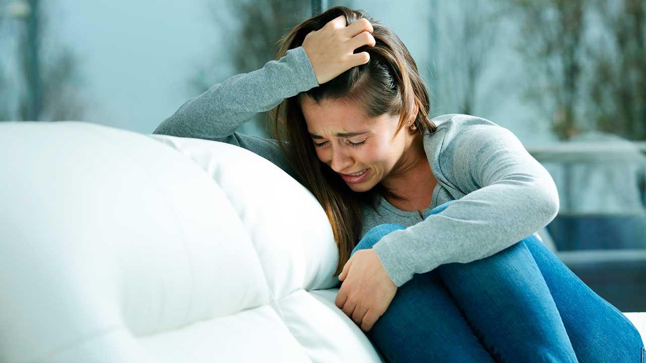 Frau sitzt weinend auf dem Sofa