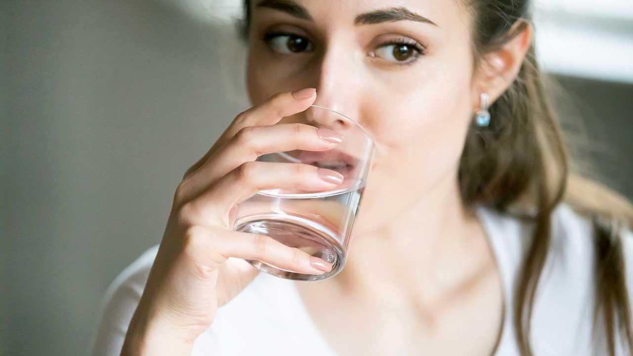 Junge Frau trinkt ein Glas Wasser