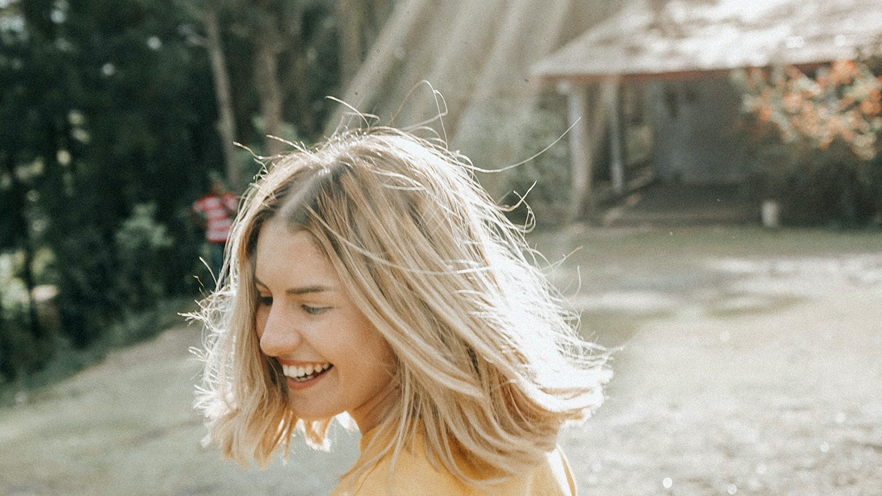 Sonnenstrahlen scheinen auf lächelnde Frau