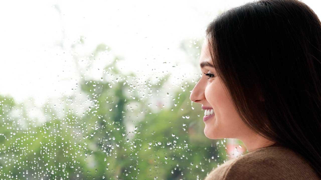 Frau blickt lächelnd aus dem Fenster, hinter der Scheibe mit Regentropfen sind verschwommen Bäume