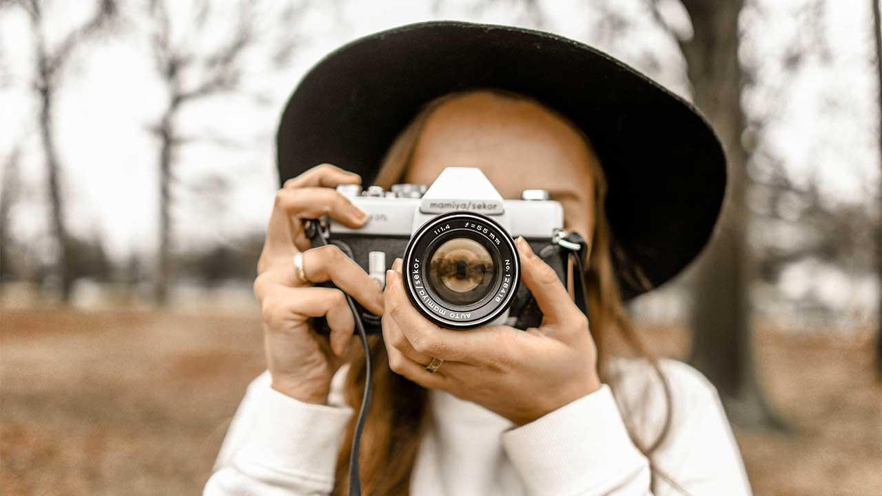 Frau hält Kamera vor Gesicht und fotografiert